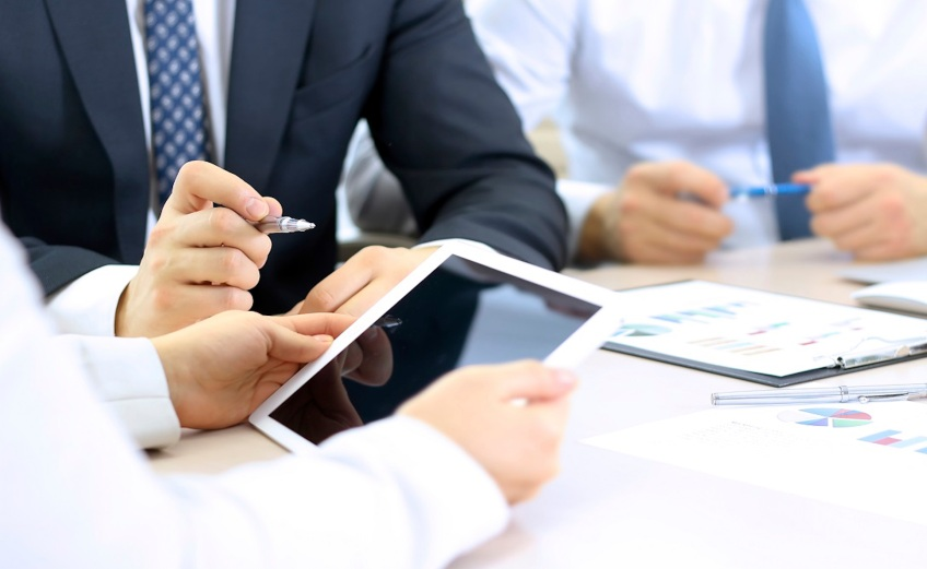 business colleagues working together and analyzing financial figures on a digital tablet